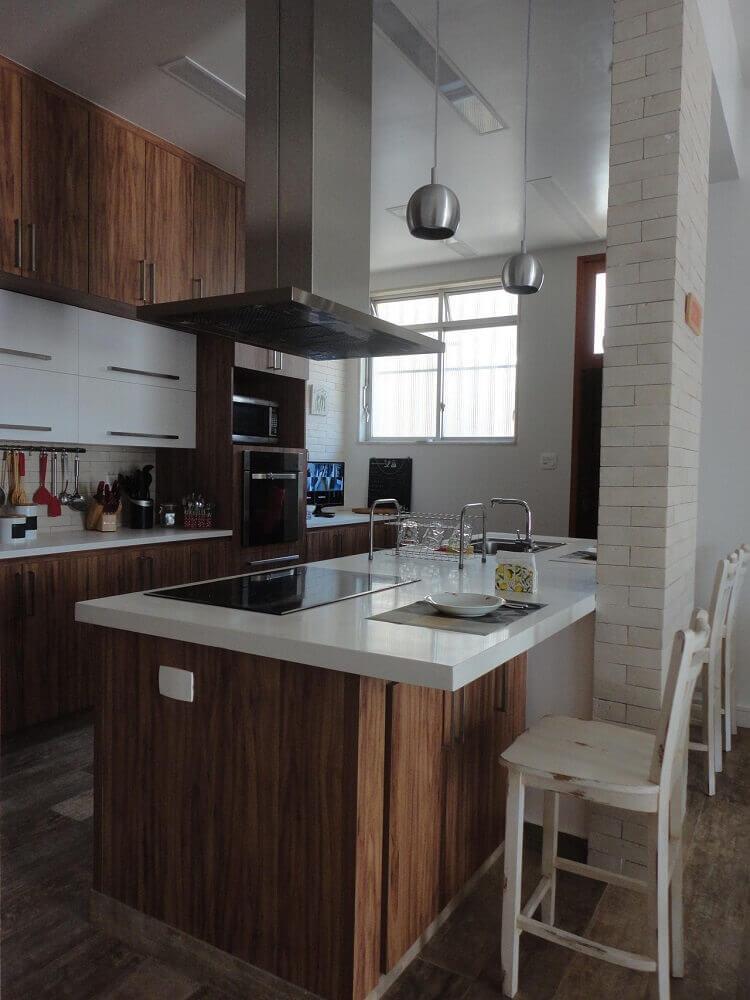 cozinha de madeira com coifa de alumínio