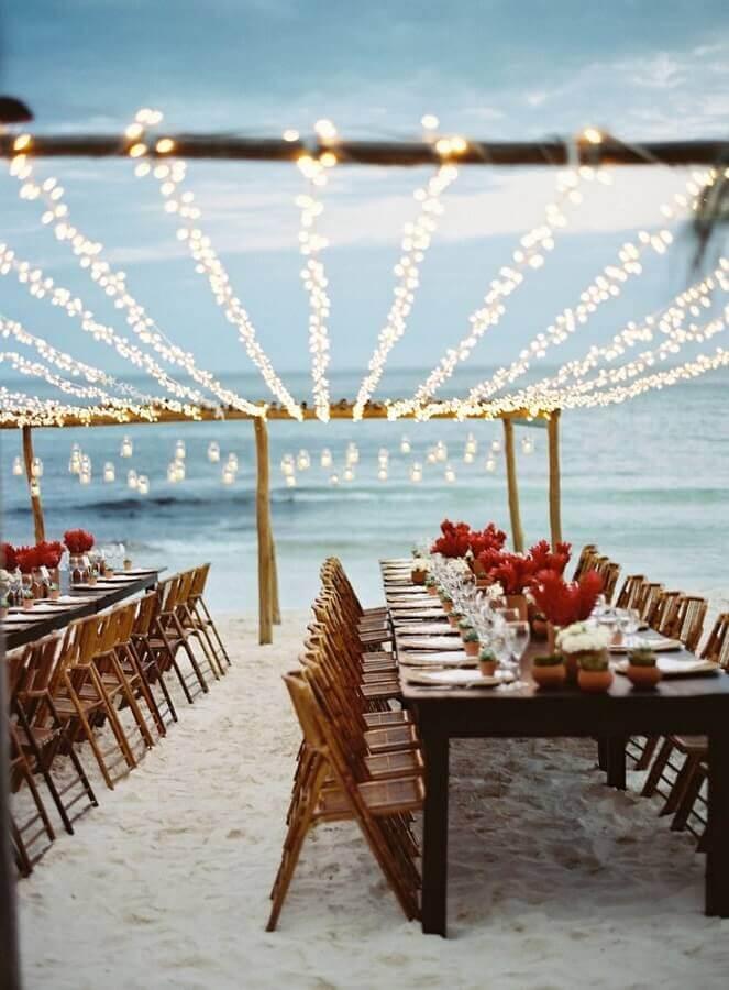 decoração de casamento na praia com flores vermelhas
