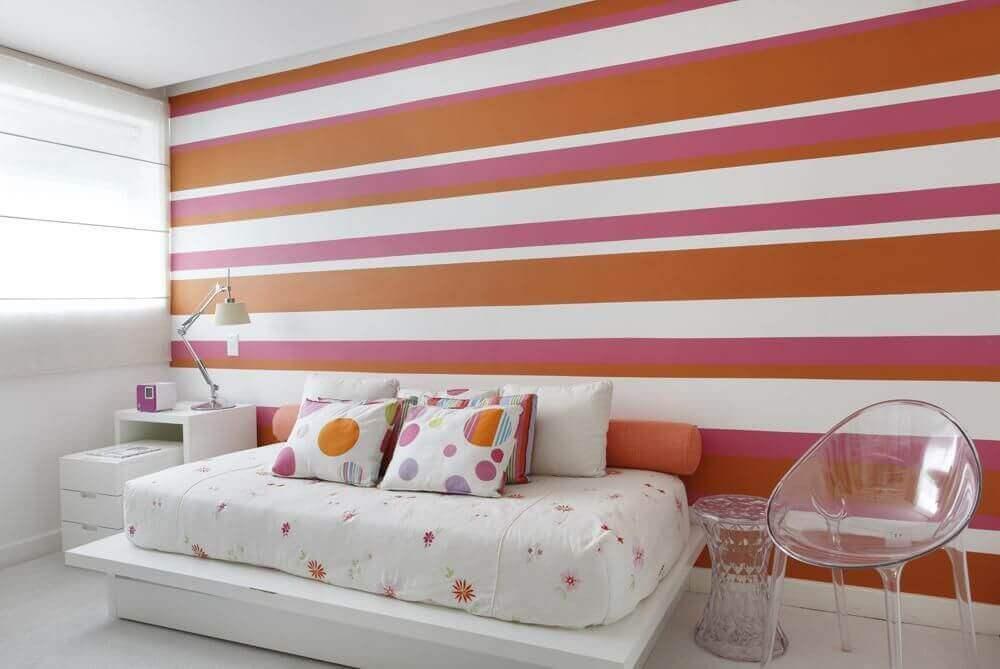 decoração de quarto feminino com papel de parede listrado de rosa laranja e branco