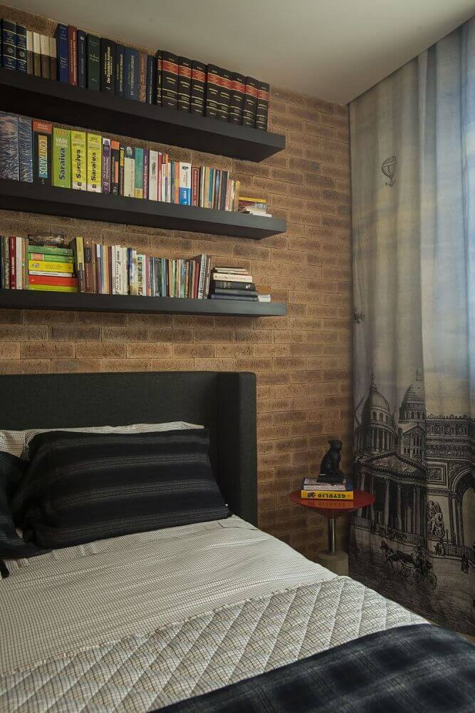 Decoração de quarto masculino com parede de tijolinho e prateleira de livros