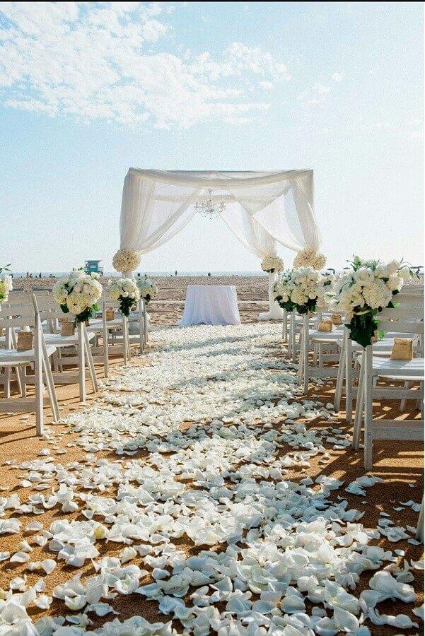 decoração rústica com pétalas de flores brancas e arranjos de rosas para casamento na praia Foto Pinterest