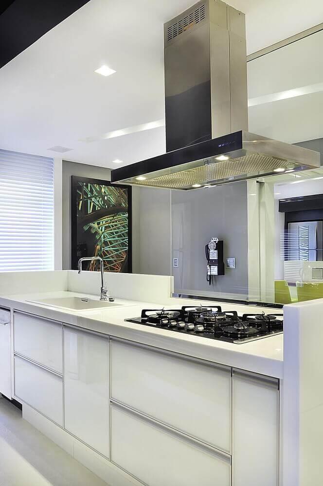 decoração de cozinha planejada com coifa de alumínio e iluminação embutida