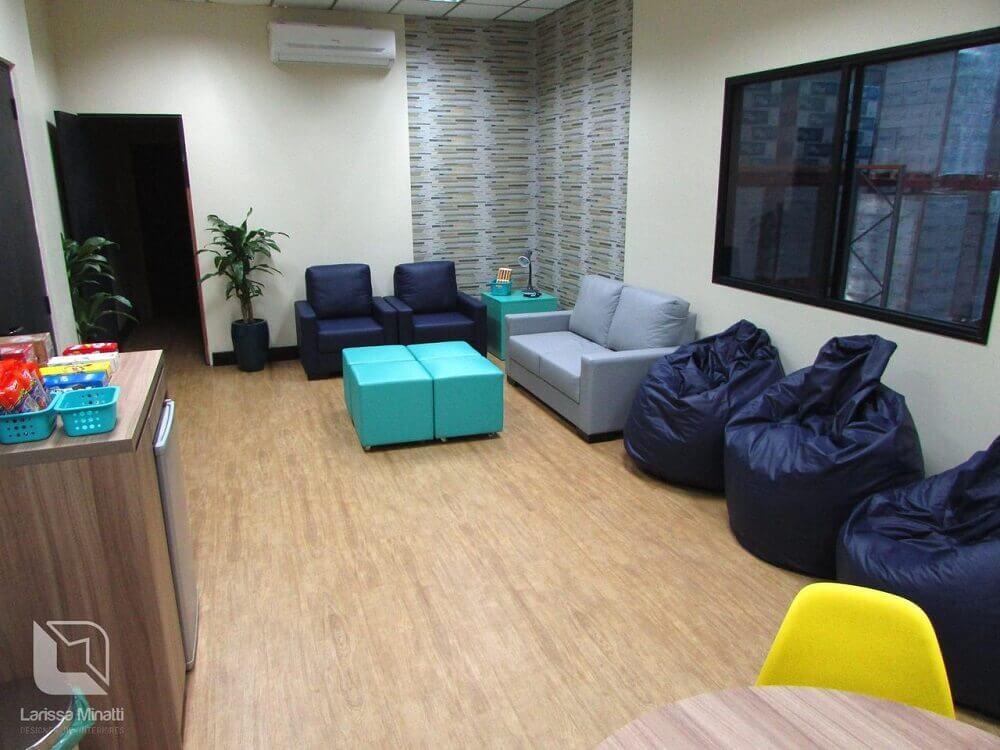 decoração de sala de descompressão com sofás e puff grande