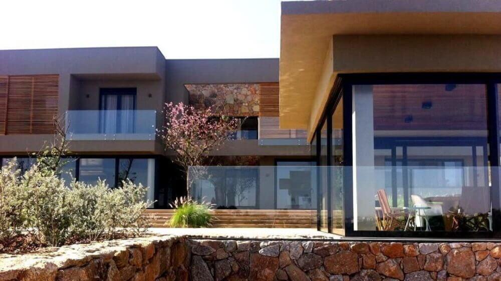 fachada com telhado platibanda e revestimento de pedras
