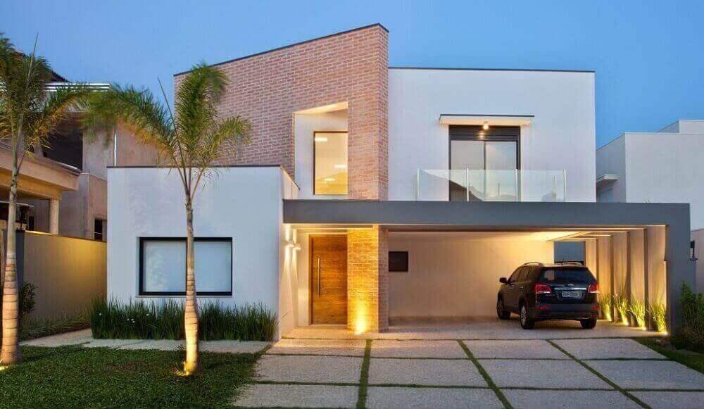 fachada de casa moderna com telhado platibanda e tijolo a vista