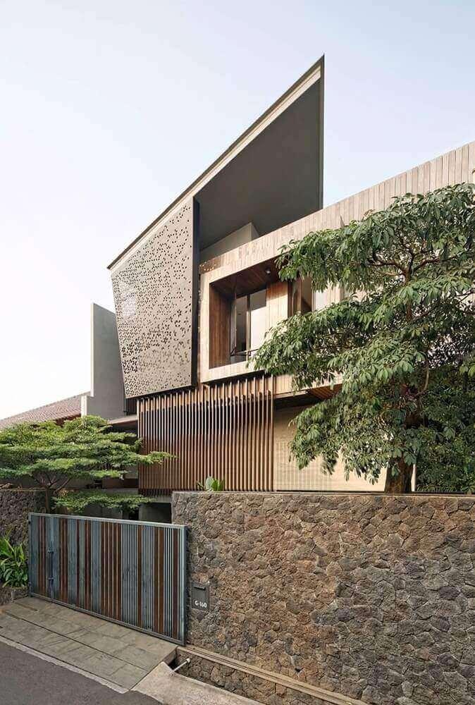 frente de casas com muro de pedra e detalhes em madeira