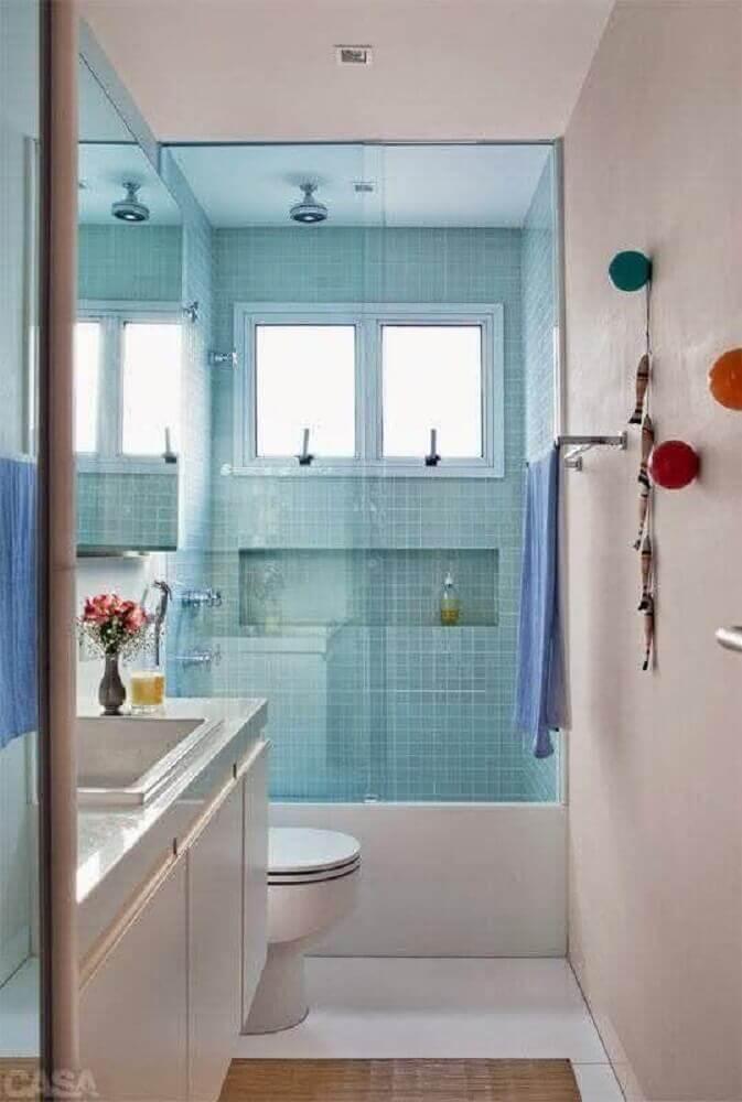 modelo de banheiro pequeno com nicho embutido e revestimento azul no box