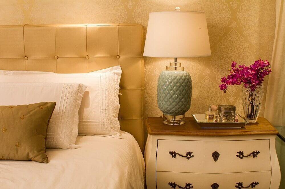quarto com cabeceira estofada dourada