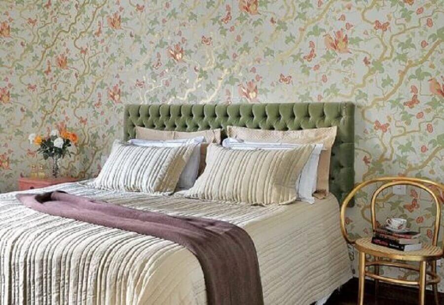 quarto com papel de parede floral e cabeceira estofada verde