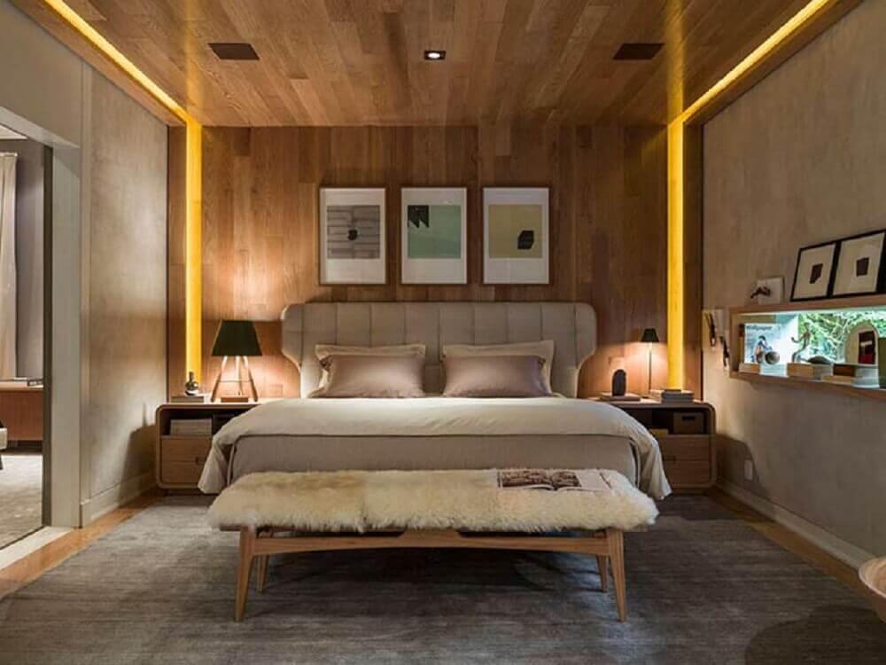 quarto com parede revestida de madeira e cabeceira estofada bege
