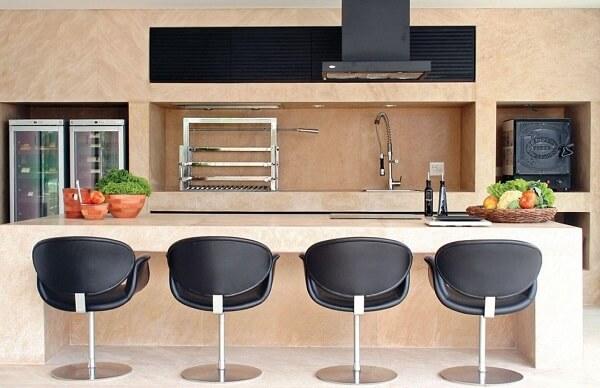 Área de churrasco com torneira gourmet e poltronas na cor preta
