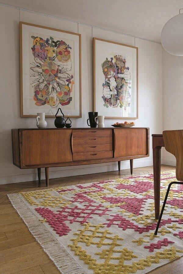 O móvel 100% em madeiradá uma certa rusticidade à sala que conta com detalhes coloridos