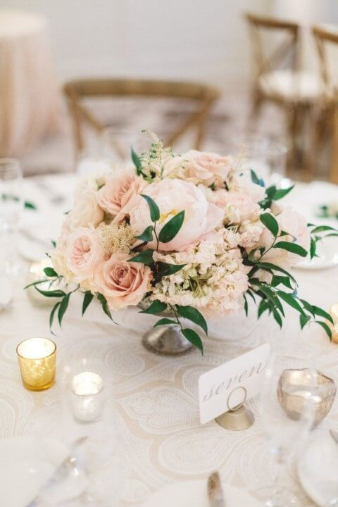 Centro de mesa de casamento com flores claras e folhas