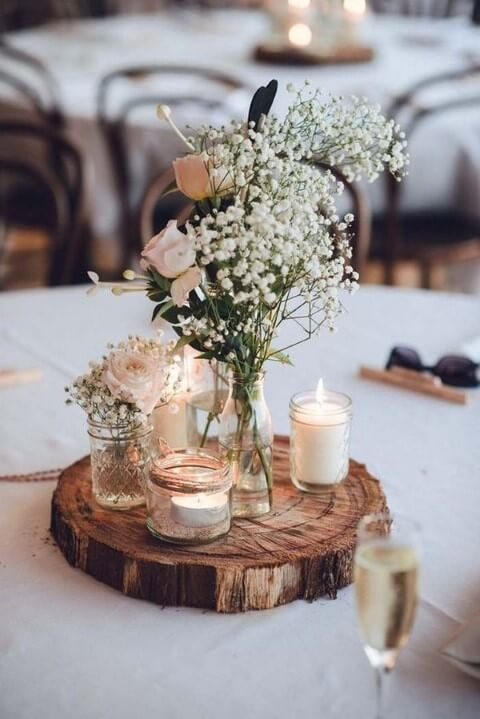 Centro de mesa de casamento rústico com base de madeira, velas e flores