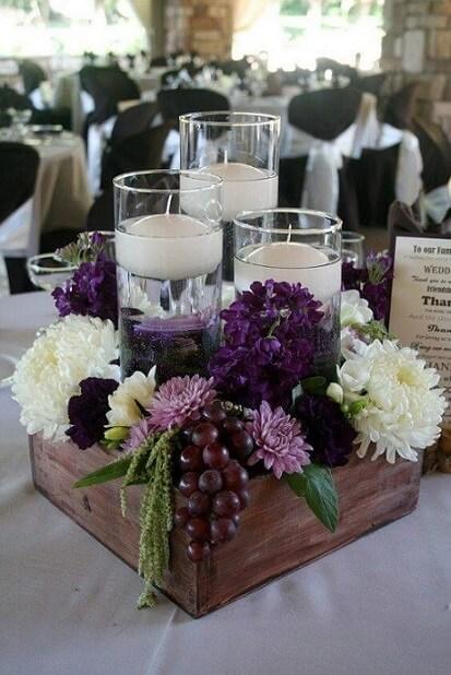 Centro de mesa de casamento rústico com velas e flores
