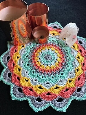 Centro de mesa de crochê colorido com velas e cristal