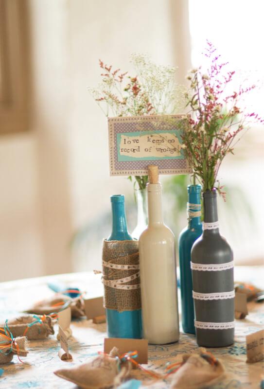 Centro de mesa de garrafa com flores e recado