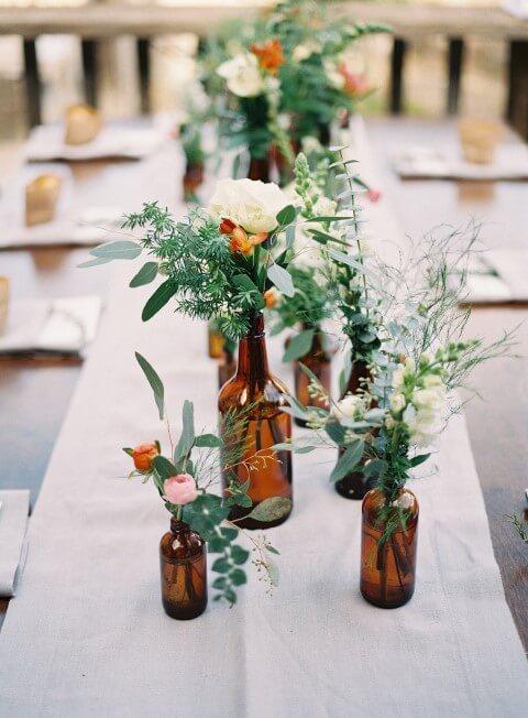Centro de mesa de garrafa de tamanhos diferentes e flores