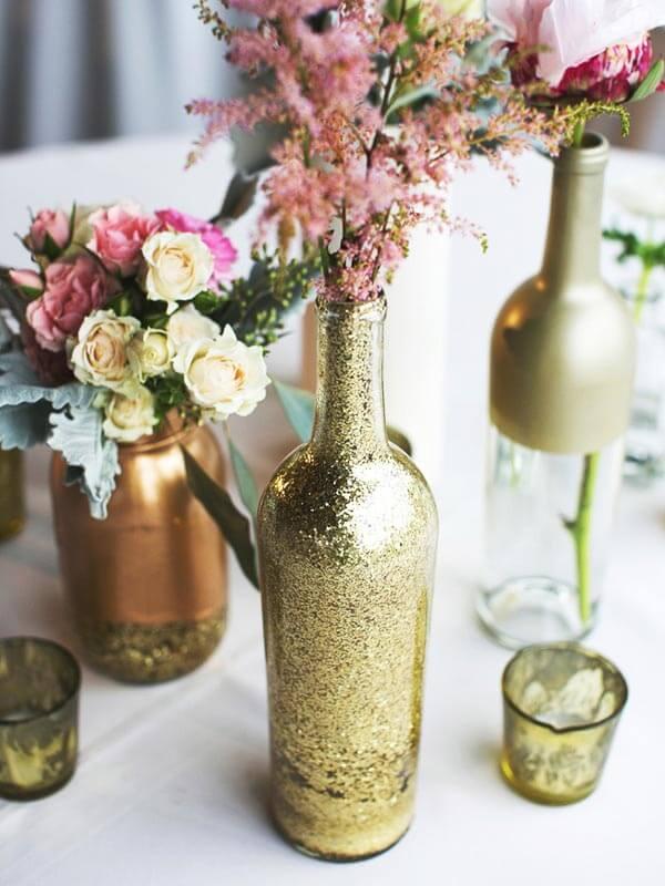 Centro de mesa de garrafa douradas e flores