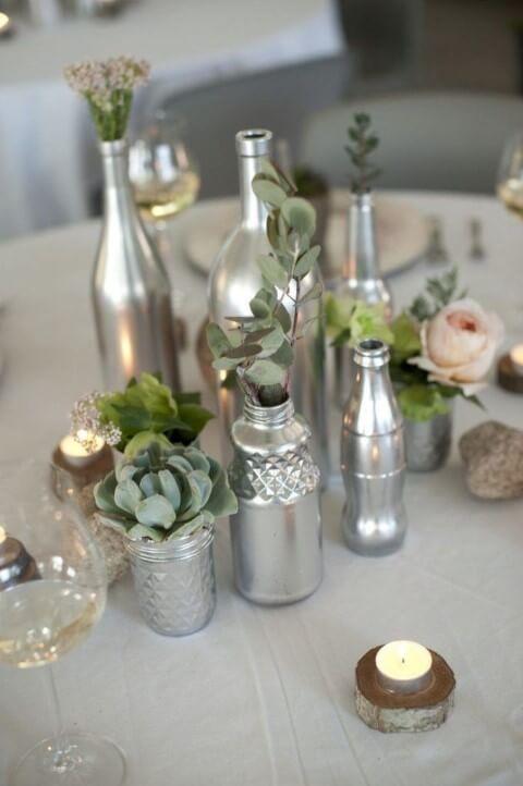 Centro de mesa de garrafa metálica e plantas