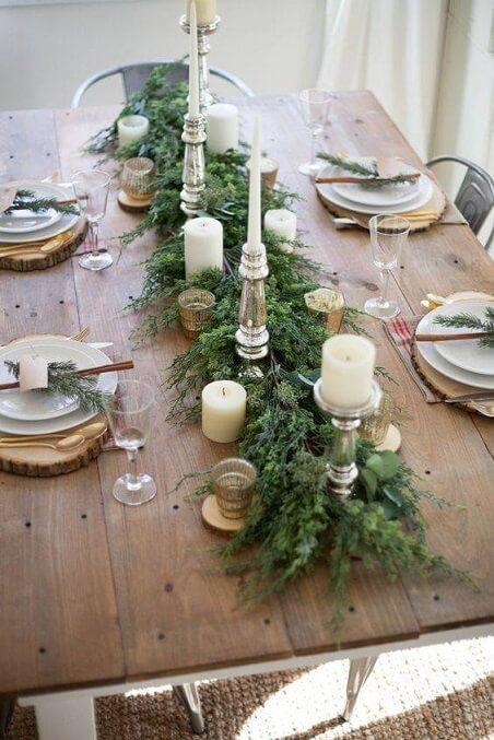 Centro de mesa de jantar rústico com velas e ramos de folhas