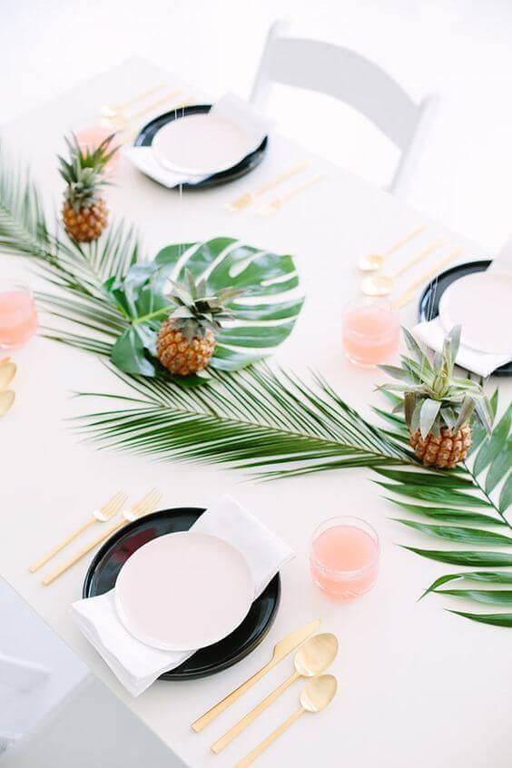 Centro de mesa tropical com folhas e frutas para festa