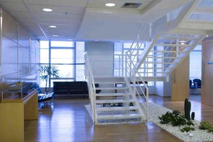 Espaço comercial com escada de ferro branco Projeto de Artiun Arquitetura