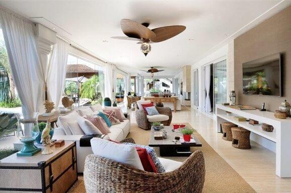 Poltronas para sala de estar com acabamento de palha com almofadas Projeto de Quitete Faria