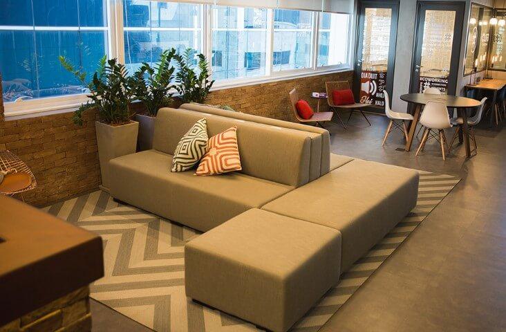 Recepção de coworking com sofás e mesa