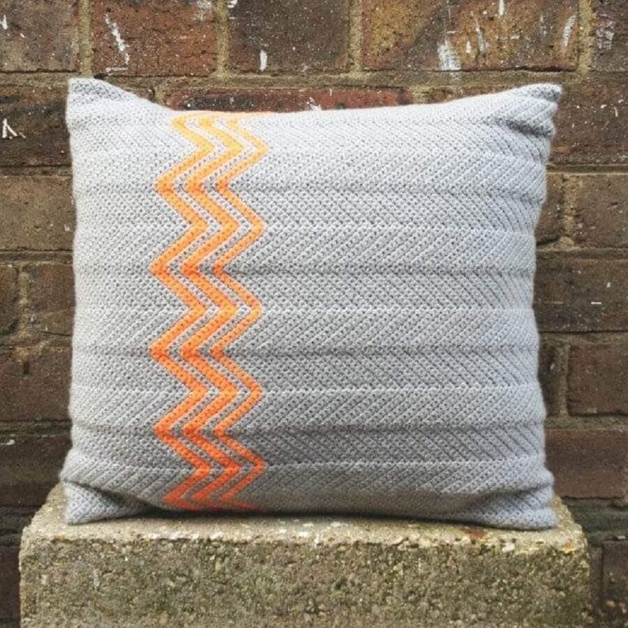 almofada de crochê cinza com detalhes geométricos laranja