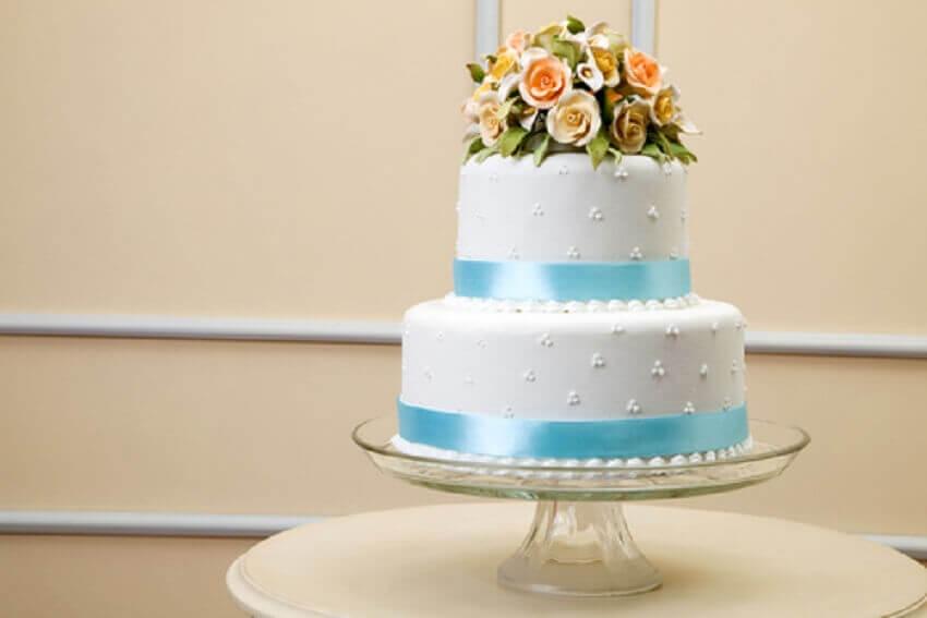 Bolo de casamento 2 andares com decoração azul e branca e topo de flores