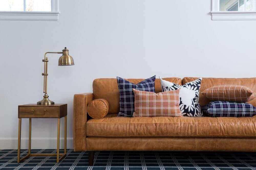 decoração com sofá de couro para sala com muitas almofadas