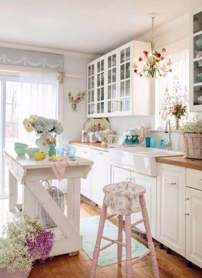 Cozinha Provençal com detalhes delicados como vasos de plantas, louças de porcelana, puxadores delicados entre outros.