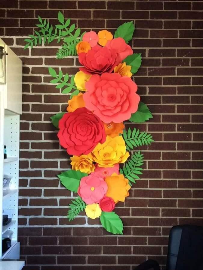 parede de tijolinho decorada com maxi flor de papel coloridas