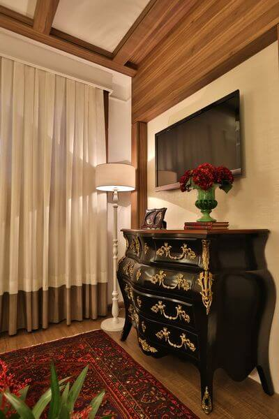Cômoda retrô preta com detalhes dourados em quarto de casal Projeto de Majo Arquitetura