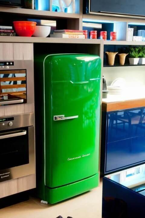 Cozinha com móveis azuis e geladeira colorida verde Projeto de Juliana Pippi
