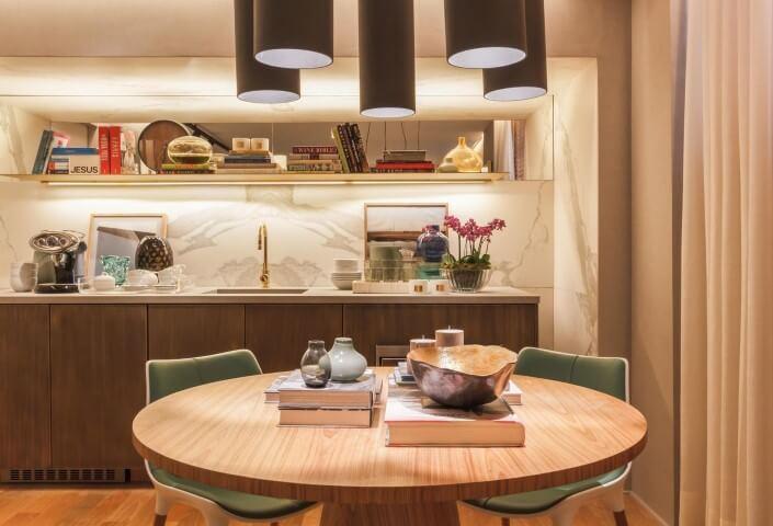 Cozinha planejada com mesa redonda de madeira e cadeiras verdes Projeto de Bruno Gap