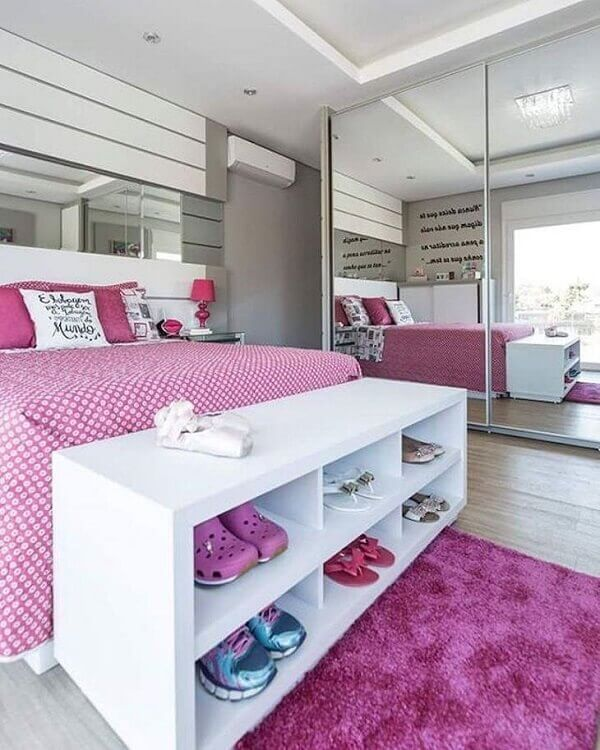 Estrutura um móvel ao pé da cama como modelo de sapateira