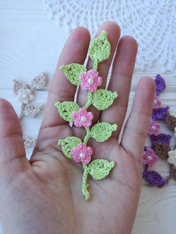 Folhas e flores pequeninas de crochê formam um lindo arranjo