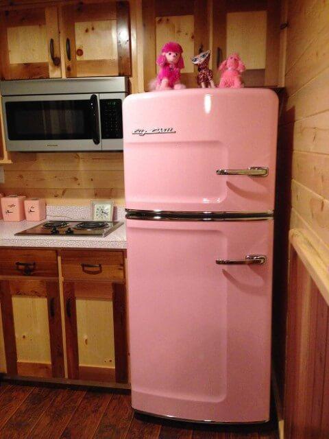 Geladeira colorida cor de rosa em cozinha com móveis de madeira