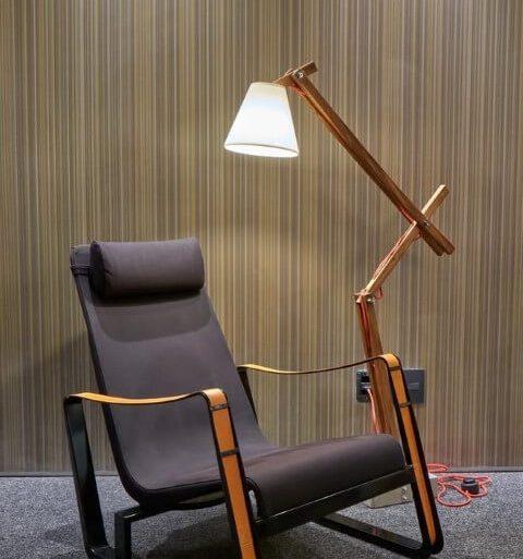 Luminária de madeira ao lado de poltrona preta Projeto de Arca Loja Conceito