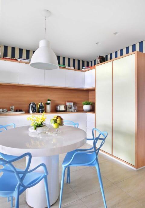 Mesa redonda branca com cadeiras azuis com pendente em cima Projeto de Ana Yoshida