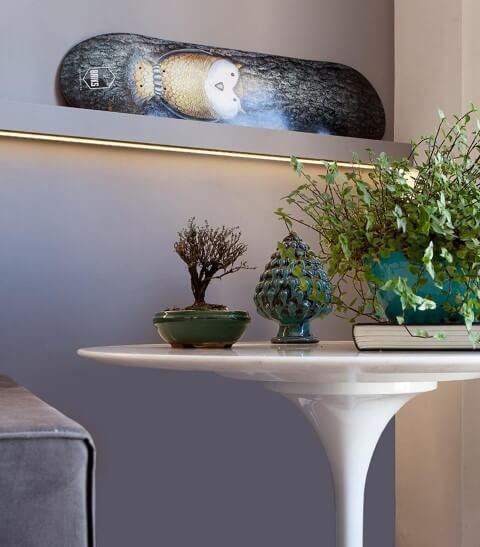 Mesa redonda branca lateral com objetos de decoração ao lado do sofá