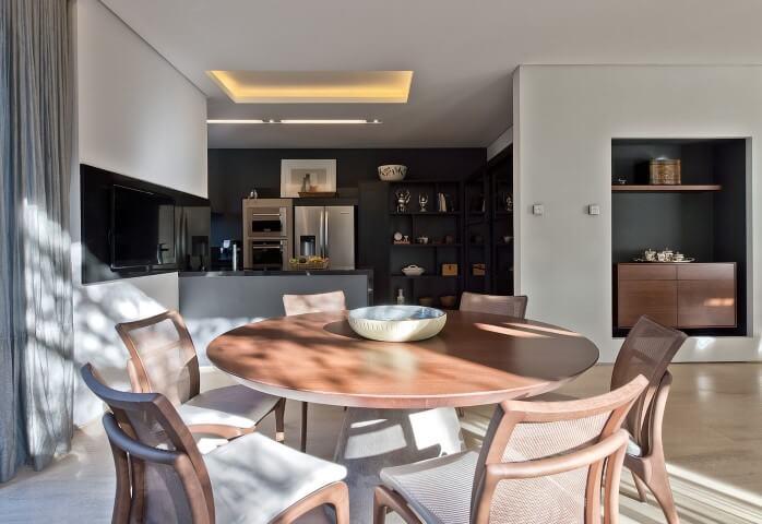 Mesa redonda de jantar de madeira com 6 cadeiras e objeto de decoração no centro Projeto de Leonardo Muller
