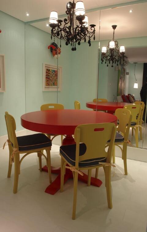 Mesa redonda de jantar vermelha com cadeiras amarelas Projeto de Luiz Humberto de Albuquerque