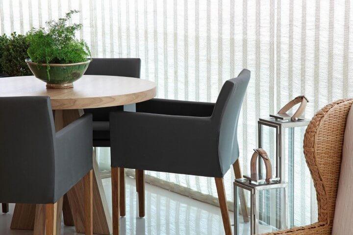 Mesa redonda de madeira e poltronas pretas Projeto de Negrelli e Teixeira