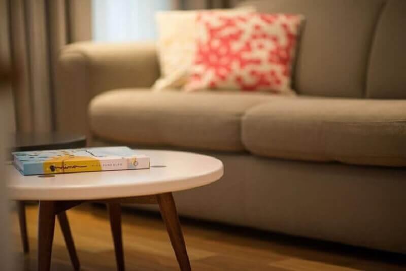 Sala de estar com mesa redonda de centro branca com pés de madeira