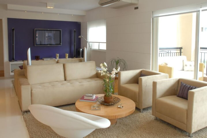 Sala de estar com mesa redonda de centro branca e móveis bege Projeto de Teresinha Nigri