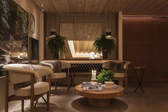 Sala de estar com mesa redonda de centro de madeira e poltronas Projeto de Bruno Gap