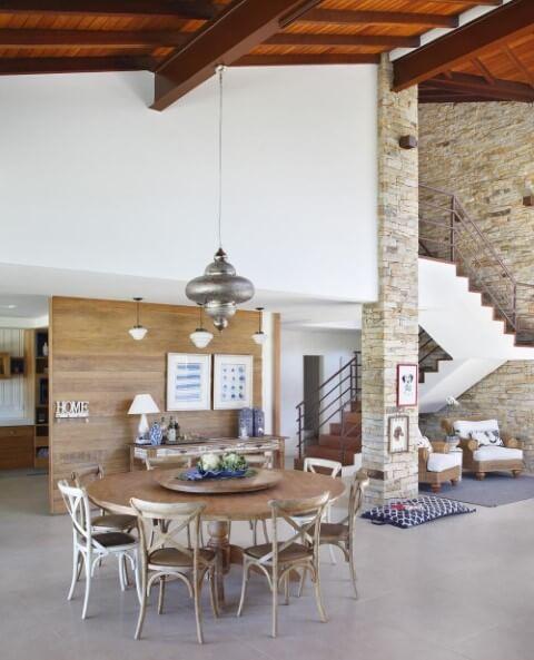 Sala de estar com mesa redonda de madeira ampla com várias cadeiras Projeto de RBP Arquitetura